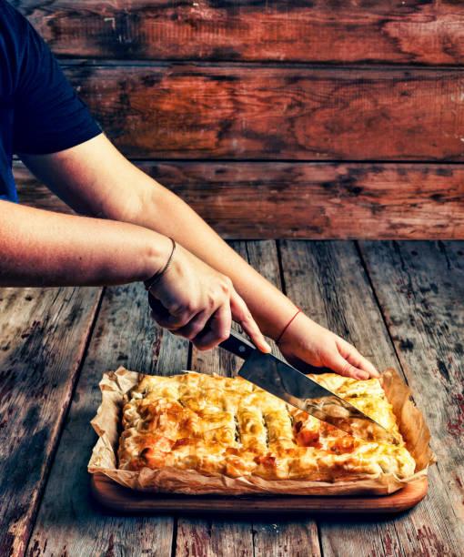 hausmannskost. die hände von frauen schneiden hausgemachte kuchen mit füllung. u.s. unabhängigkeitstag - waffelbecherkuchen stock-fotos und bilder