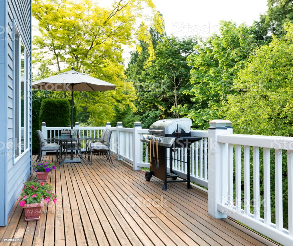 Home deck and patio with outdoor furniture and BBQ cooker with bottled beer stock photo