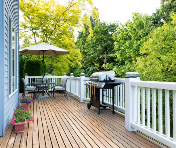 ホーム デッキ、屋外用家具付きパティオ、瓶ビールとバーベキュー コンロ - デッキ ストックフォトと画像