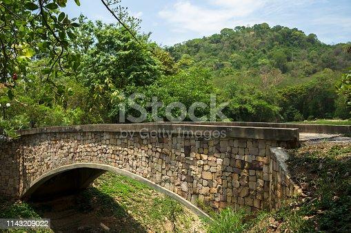 Concrete bridge crossing the pond In a public park