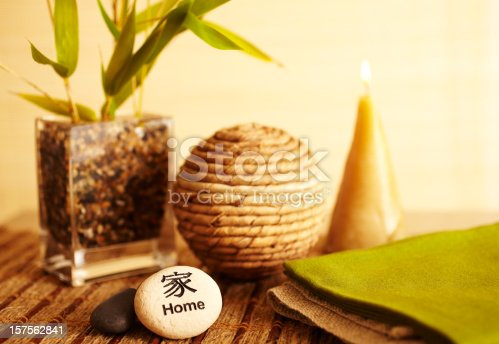Home decor still life of home river rock with bamboo in vase with wicker ball, candle and river stones close-up