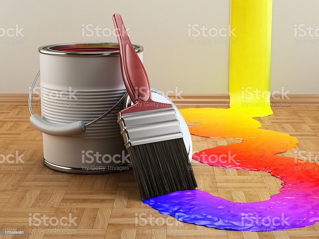 Paint can and paintbrush with multi-colored paint on the wooden...