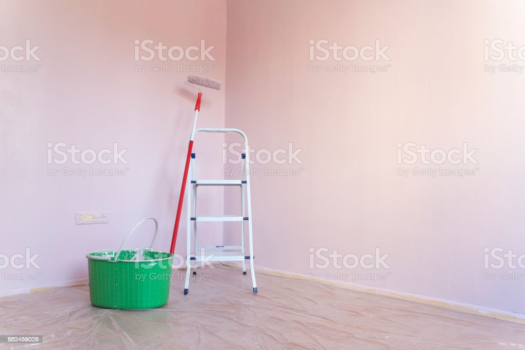 Metal ladder with paint can and roller