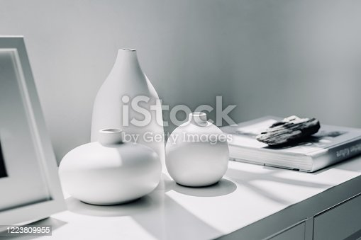 Home decoration of neutral coloured vases and picture frame on a cabinet by the window in sunlight