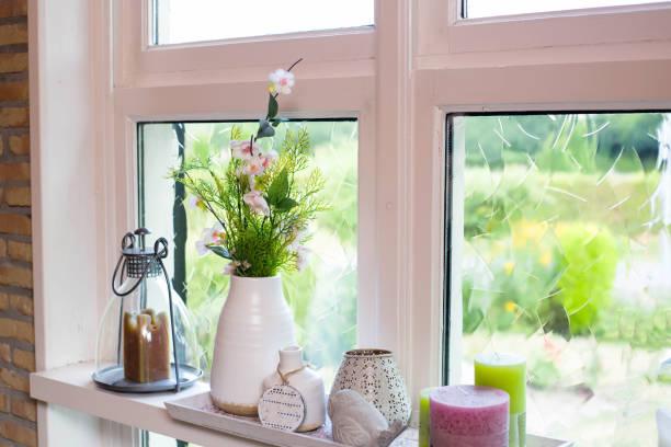 hause dekoration auf der fensterbank mit bunten blumen und weiße vase an einem sonnigen tag - indoor feen gärten stock-fotos und bilder
