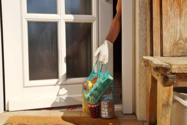 home delivering some groceries to an man at quarantine time because of coronavirus infection sars-cov-2. the man's hand is taking a shopping bag at he front door. food delivery in net bag at door of home for self isolation coronavirus recovery. - food delivery zdjęcia i obrazy z banku zdjęć