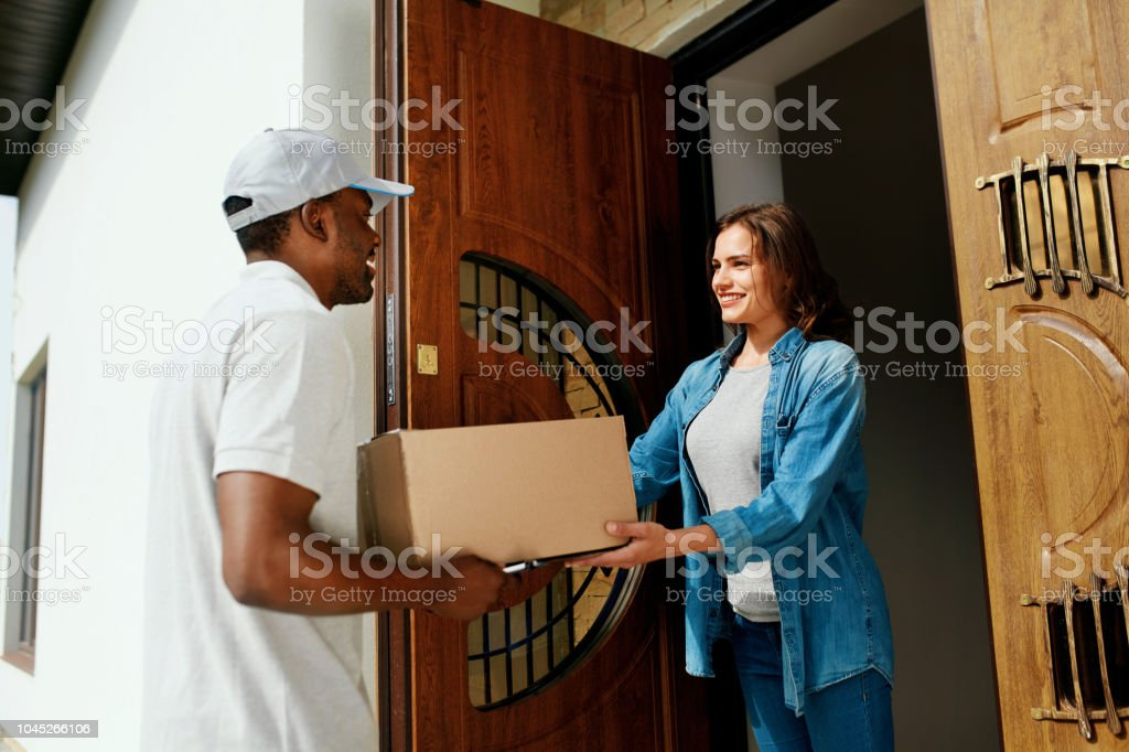 Home Delivery. Courier Delivering Package To Client. Smiling Woman...