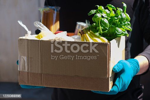 Home delivery during an epidemic. contactless delivery. Food donation. Men's hands hold a box with products