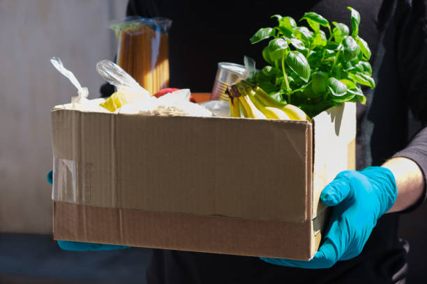 Home delivery during an epidemic. contactless delivery. Food donation. Men's hands hold a box with products. Home delivery during an epidemic. contactless delivery. Food donation. Men's hands hold a box with products charitable donation stock pictures, royalty-free photos & images