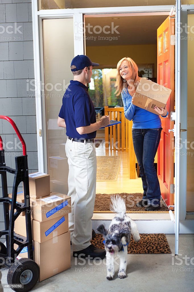 Home Delivery Man Deliverying Packages to Woman Customer's Front Door stock photo