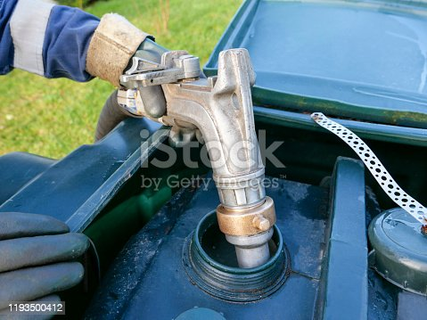 An oil delivery driver filling up a residential oil tank. He is delivering to a rural location in Scotland, where mains gas is not connected. The man is wearing protective overalls and gloves as he carefully fills the green plastic tank with home heating oil, in preparation for the winter months. He is squeezing a metal nozzle attached to a long rubber hose that runs from his oil delivery lorry parked nearby to maintain control of the amount being delivered.
