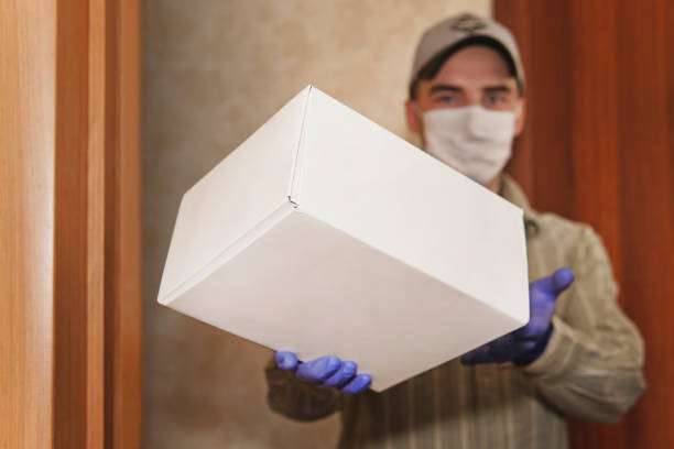home delivery, online order. man in a medical mask and rubber gloves with white box, a parcel in his hands. delivery during the quarantine of the coronavirus pandemic copy space stock photo