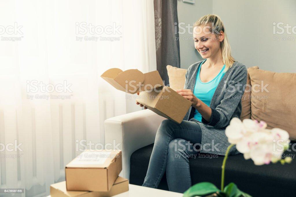 entrega a domicilio - sonriendo caja de cartón de apertura de joven - foto de stock