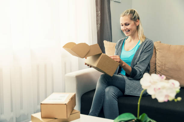 home delivery - smiling young woman opening cardboard box stock photo