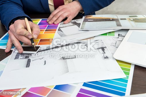 895150806 istock photo Home designer work at office house sketch with color catalog for dream modern renovation apartment. Archtecture house plan and color sample 1212969129
