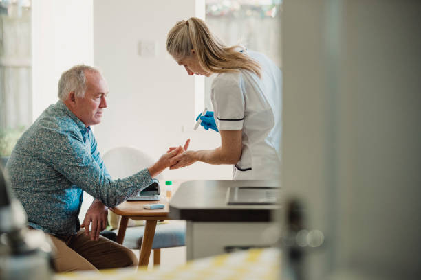 Home Diabetes Treatment Senior diabetic man is having a check up at home from a district nurse. She is checking his blood glucose levels. hypoglycemia stock pictures, royalty-free photos & images