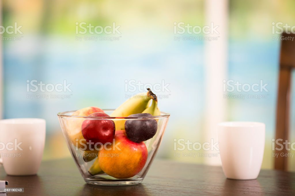 Home dining table. Fruit bowl, coffee mugs, window. Nobody. stock photo