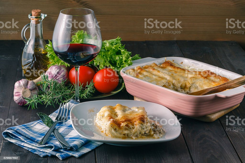 Home dinner with lasagne and wine stock photo