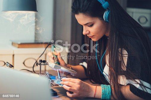 Teenage girl soldering circuit board at home
