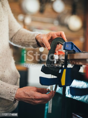 Hands of Senior Caucasian woman working on woodworking home DIY project.