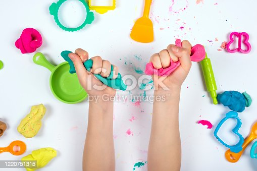 Little girl hands close up playing with pink and blue modeling clay on white background. Home Education game with clay. Top view. Early development concept