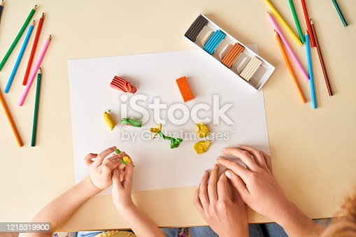 Young mother and daughter education at home sitting at table molding using modeling clay creativity development top view