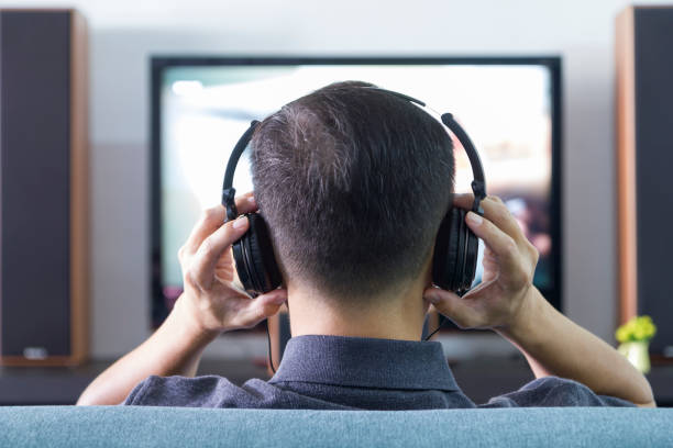 Home Entertainment Back side of an Asian man wearing black heaphones in front of blurry out-of-focus television and home entertainment system background surrounding stock pictures, royalty-free photos & images