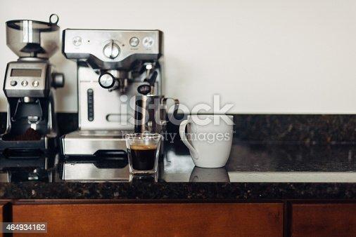 Home setup for making espresso and lattes: coffee bean grinder, espresso machine, shot of espresso, and mug. With space for copy.