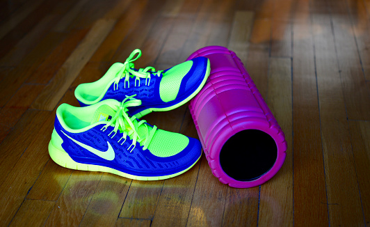 New York,  USA - December 10, 2015: Home exercise equipment - Nike Free Run+ Men's Running Shoes and a Foam Roller on a wooden floor at home.