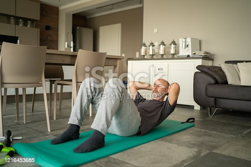 fitness workout at home during coronavirus curfew, mature adult man doing abdominal exercises on gym mat alone in his living room