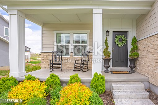Home facade with stairs leading to porch with pillars and gray door with wreath. Front entrance view of a house with bright green plants on the front yard.