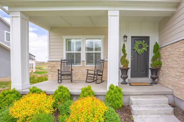 hem fasad med trappor som leder till veranda med pelare och grå dörr med krans - fasad bildbanksfoton och bilder