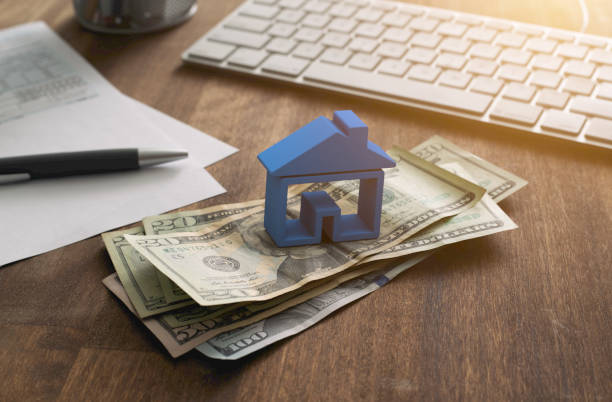 Home Finance Mortgage and Taxes Deduction 3D house on pile of money with tax and financial forms on the desk. refund stock pictures, royalty-free photos & images