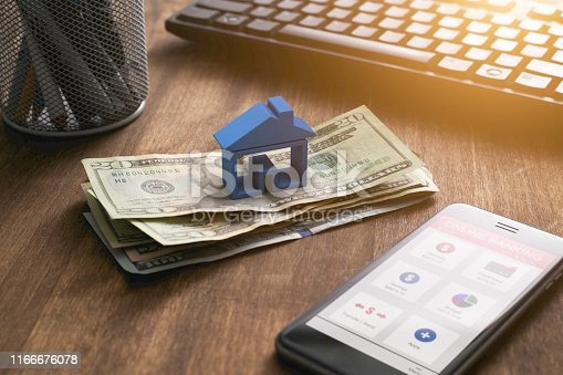 3D house on a pile of cash with keyboard and smart phone with online banking app.