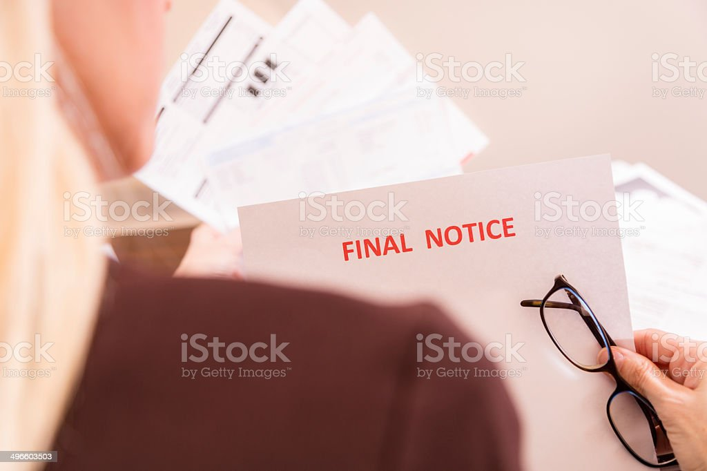 Home Finances: Woman struggles to pay her bills. Final notice. stock photo
