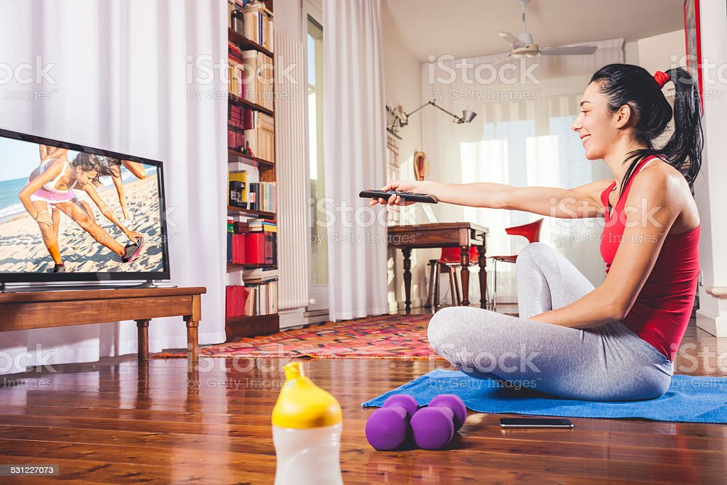 One woman exercising at home following instructions on television