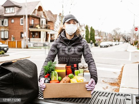 COVID-19, Young women delivers fresh food during pandemic lockdown. She is offloading box of fresh produce from the bed of the pick up truck. She is wearing face mask. Urban setting of a North American city.