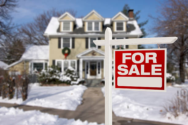 Home For Sale Sign in Front of Snowy New House Home For Sale Real Estate Sign in Front of Beautiful New House in the Snow. real estate sign stock pictures, royalty-free photos & images