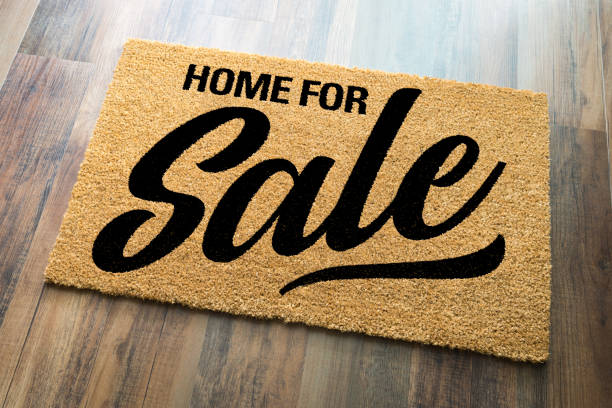 Home For Sale Welcome Mat On A Wood Floor Background stock photo