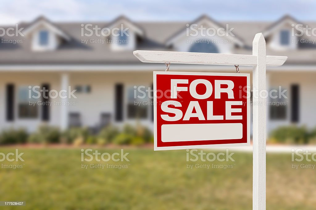 Home for sale with red for sale sign in front yard stock photo