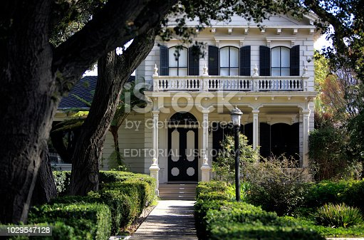 Watsonville,California,USA-  March 9,2017: White 1870's Victorian style home with Live Oak trees and boxwood hedges. Central California.