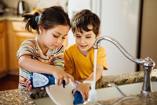 Toddlers having fun washing dishes