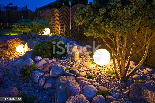 Home garden at night, illuminated by globe shaped lights. Decorative gardening and landscaping abstract.