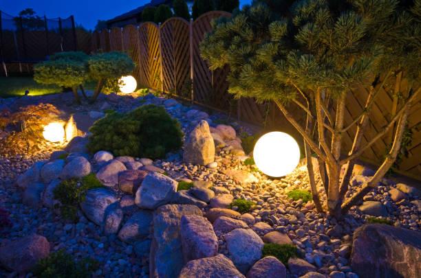 domowy ogród w nocy, oświetlony światłami w kształcie kuli ziemskiej - błyszczący zdjęcia i obrazy z banku zdjęć