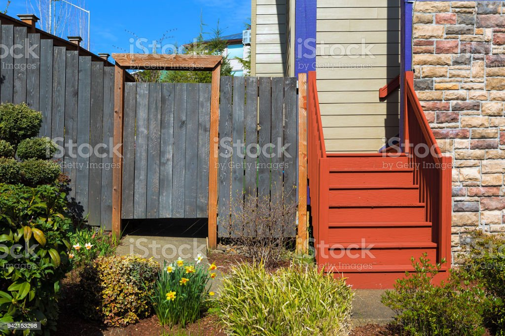 Home garden frontyard with plants wood fence gate colorful staircase sidings and stone wall stock photo