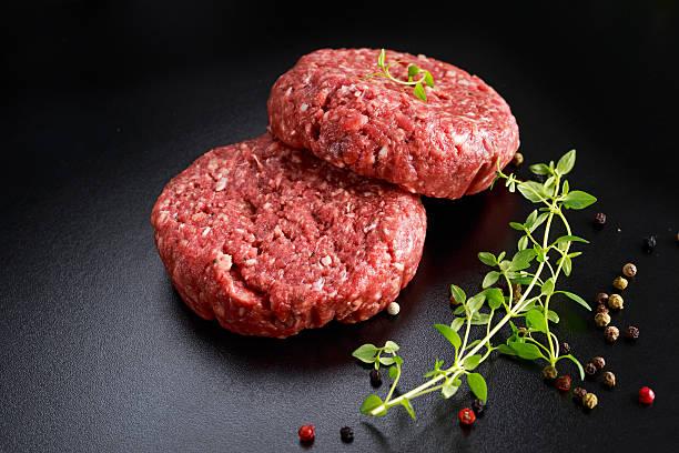 casa artesanal de carnes cruas hambúrgueres de carne bovina moída no quadro-negro - cru - fotografias e filmes do acervo