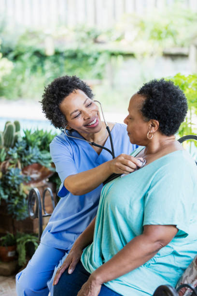 Home health aide with senior patient, using stethoscope stock photo