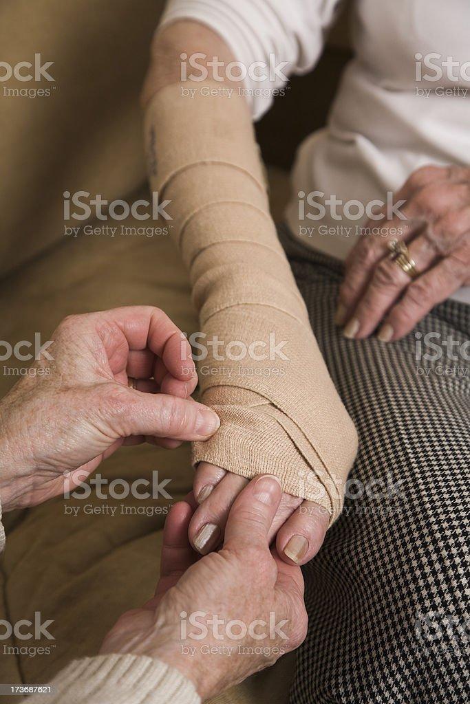 Home healthcare nurse adjusts bandage on wrist of senior woman royalty-free stock photo
