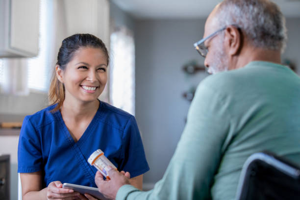 Home healthcare nurse brings new prescriptions for senior man stock photo