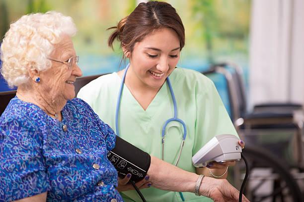 su personal de enfermería de atención médica control de la presión arterial de una mujer de edad avanzada. - geriatría fotografías e imágenes de stock
